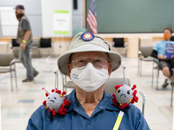 Veteran wearing hat with dangling crocheted coronavirus replicas