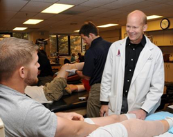 Robert LaPrade, MD, PhD consulting with a physical therapist