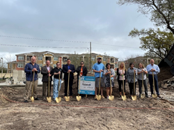 MaintenX team members and Habitat Home recipients stand holding golden shovels on freshly turned dirt the groundbreaking of a new home in Clearwater, Fla.
