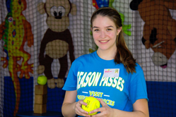 Female employee working at a baseball throwing game with stuffed animal prizes behind her.