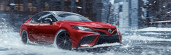 2021 Toyota Camry driving on a snow-covered road