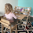 Tess enjoys her brand new Montessori-inspired RAD Children's Furniture DeskEasel and RAD Skoolhaus chair.