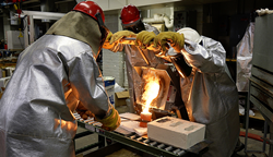 WPI researchers pour molten metal into a preheated investment casting mold.
