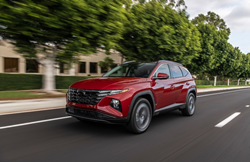 The side and front view of a red 2022 Hyundai Tucson driving down a road.