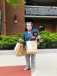 Woman standing with three bags of food with her dog in her arms.