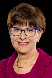 White woman with short brown hair and blue glasses, wearing gold necklace, and bright pink round collar sweater and matching jacket.