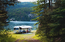 2021 Airstream International positioned in front of forest lake
