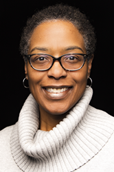 Headshot of  smiling Black woman with short curly hair, wearing brown glasses and white turtleneck on black background.