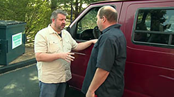 two men having a discussion in front of a commercial van